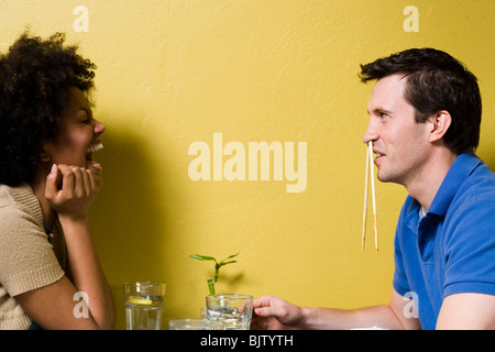 Man with chopsticks in nose at restaurant - Stockfoto