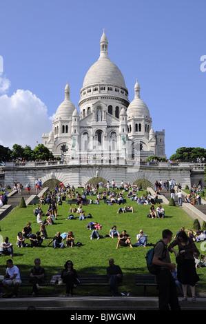Basilica Sacre Coeur with tourists on lawn Montmartre, Paris. - Stock Photo