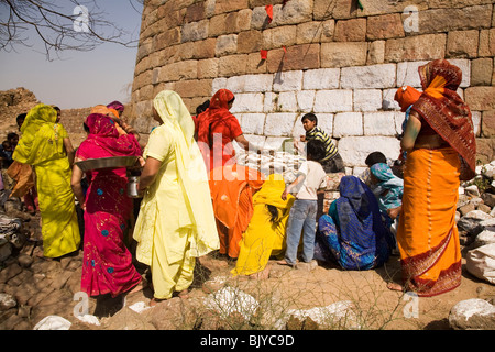 Indian women in colourful saris prepare food outside the walls of the ruined Tughluqabad Fortress in Delhi, India - Stock Photo