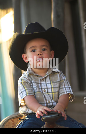 A cute 2-4 year old mixed race boy  sitting on a saddle and wearing a cowboy hat(Released) - Stock Photo