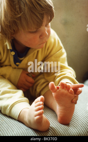 Little boy counting toes toddler exploring Toddler feet - Stock Photo