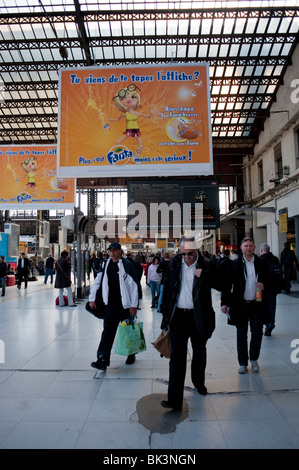 Paris, France, Businessmen Traveling in 'Gare d'Austerlitz' Train Station, with French Advertising Posters 'Fanta' - Stock Photo