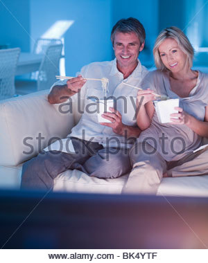 Couple eating take out food with chopsticks and watching TV on sofa - Stockfoto