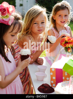 Young girls eating cupcakes at a birthday party - Stock Photo