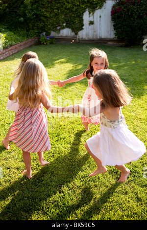 Young girls playing ring around the rosie - Stock Photo