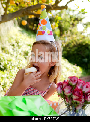 Young girl with party hat eating cupcake - Stock Photo