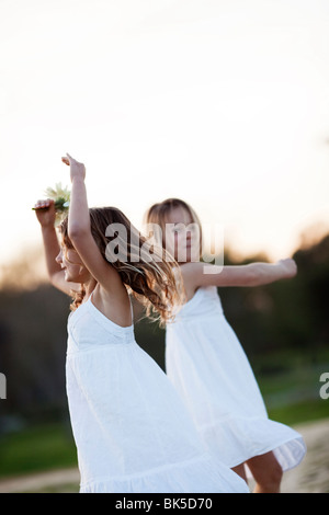 Young girls in white dresses dancing - Stock Photo