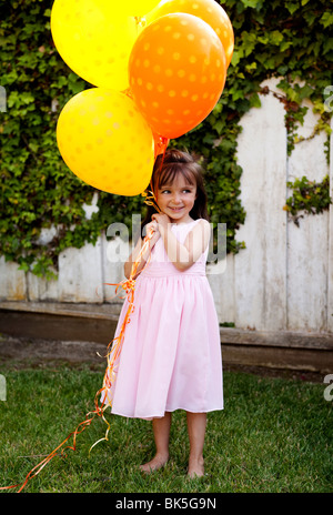 Young girl in sundress with bunch of balloons - Stock Photo