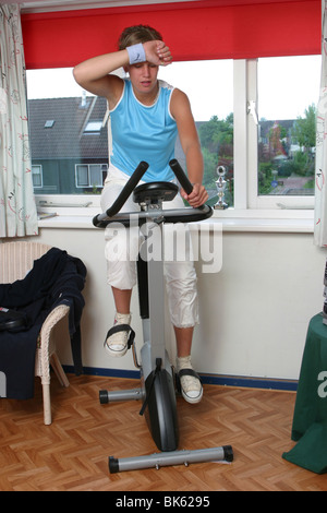Young woman fitness training at home on stationary bicycle - Stock Photo