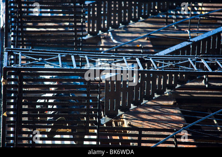 Man smoking on a fire escape in Cortlandt Alley, Tribeca, New York City - Stock Photo