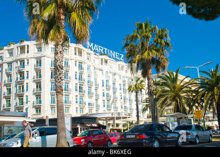 Cannes , La Croisette , the luxury hotel with frontage & balconies & palm trees & deep blue sky - Stock Photo
