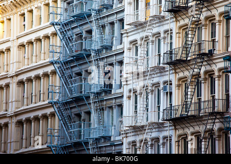 Two men on a fire escape in Soho in New York City - Stock Photo