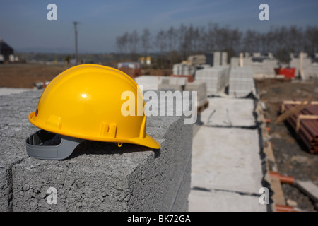 hard hat sitting on a pile of breeze concrete building blocks on construction building site in northern ireland - Stock Photo