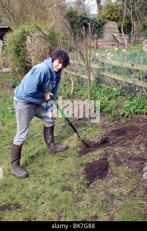 Model released teenage boy digging hole in garden - Stock Photo