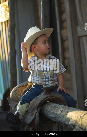 A cute 2-4 year old mixed race boy sitting on a saddle wearing a cowboy hat(Released) - Stock Photo