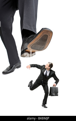 An afraid businessman running away from a big foot - Stock Photo