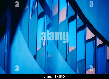 Abstract view of a modern corporate office building including reflections in the windows of the sunset sky - Stock Photo