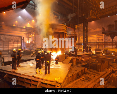 Steel Workers In Plant Working On Ladle - Stock Photo