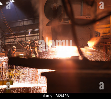 Workers Pouring Molten Steel In Plant - Stock Photo