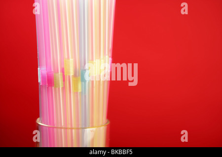 Colorful plastic drink straw over red copy space background - Stock Photo