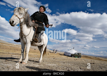 Nomad man in front of his ger (yurt or felt tent) near Tavan Bogd National Park, western Mongolia. - Stock Photo