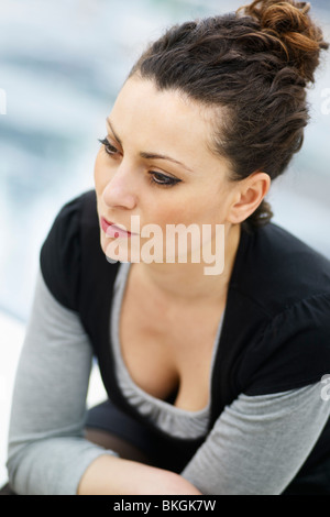 caucasian woman sitting outdoors and looking away - Stockfoto