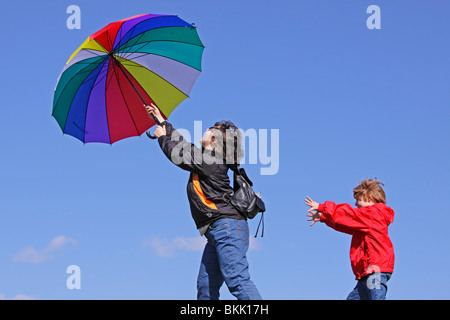 young boy trying to catch his mother who is being blown away by the wind - Stockfoto