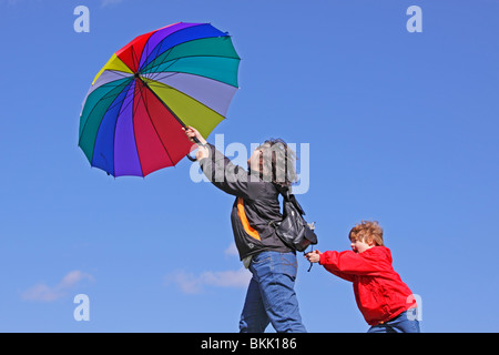 young boy holding on to his mother who is being blown away by the wind - Stockfoto