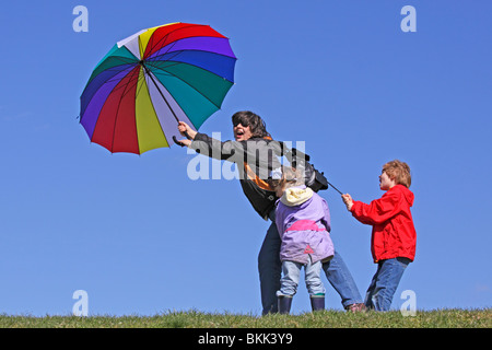 children holding on to their mother who is being blown away by the wind - Stockfoto