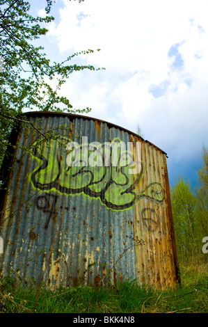 Tagging or graffiti sprayed onto an old corrugated tin hut - Stock Photo