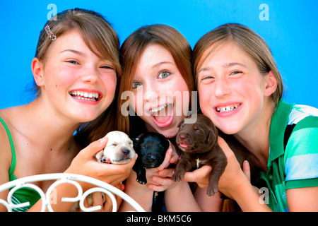 Three Girls Holding Small Puppies - Stock Photo