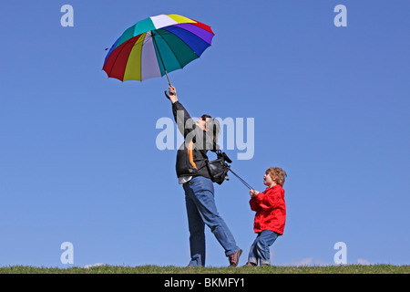 young boy holding on to his mother who is being blown away by the wind - Stock Photo