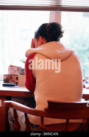 Young woman in distress sitting at table , rear view - Stockfoto