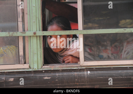 Young girl looks out of a bus window in Kolkata - Stockfoto