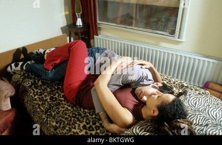 Couple in bed hug hugging - Stock Photo