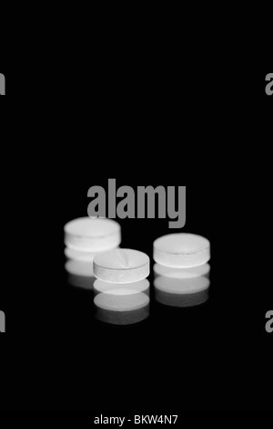 White tablets on a black background - Stock Photo