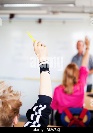 Students raising their hands - Stock Photo