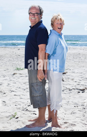 Elderly couple standing back to back - Stock Photo