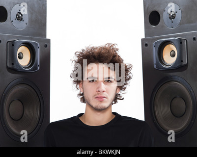 studio portrait of a one caucasian young man listening to music lover with speakerphones isolated on white background - Stockfoto