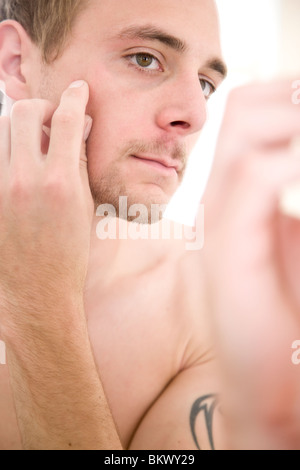 Close up portrait of young man looking into the mirror - Stockfoto