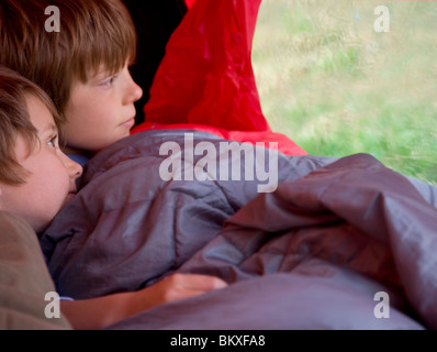 Portrait of two boys sitting in a tent looking out - Stock Photo