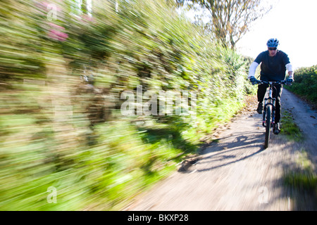 Man cycling on a country road - Stock Photo