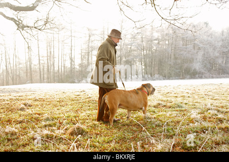 Profile of a mature man walking a dog in the park - Stock Photo