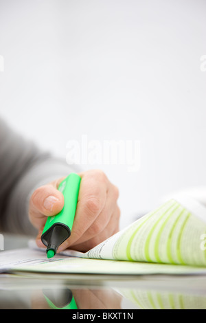 Close up of a woman hand holding a green highlighter over a paper document - Stock Photo