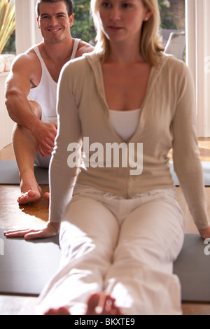 Smiling man and woman sitting on yoga mats - Stock Photo