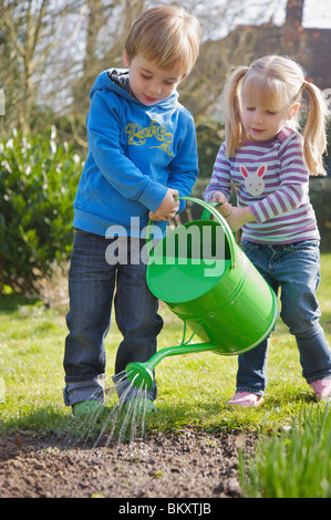 Boy and girl watering seedlings with watering can - Stock Photo
