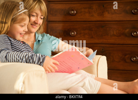 Smiling girl reading book with her mother - Stock Photo