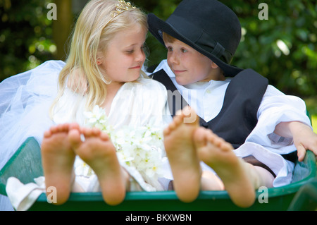 Boy and a girl wearing bride and groom costumes sitting in a wheelbarrow looking at each other - Stockfoto