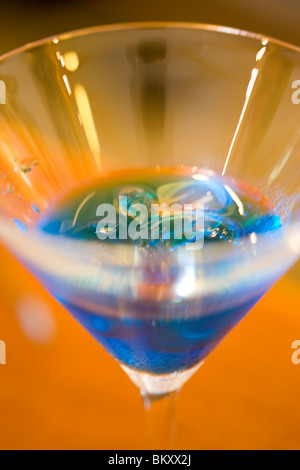 Close up of a martini glass with blue liquor and ice - Stock Photo