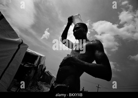 An earthquake survivor washing his body next to tents made of sheets at a temporary makeshift dwelling in Port au - Stock Photo